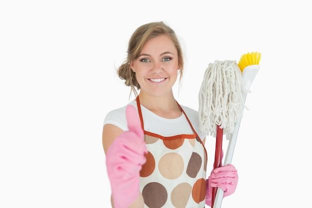 Portrait de femme de ménage avec des fournitures de nettoyage gesticulant signe pouce en l'air