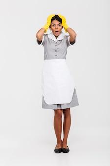 Portrait de femme de ménage surprise en uniforme gris et gants de protection jaunes tenant sa tête