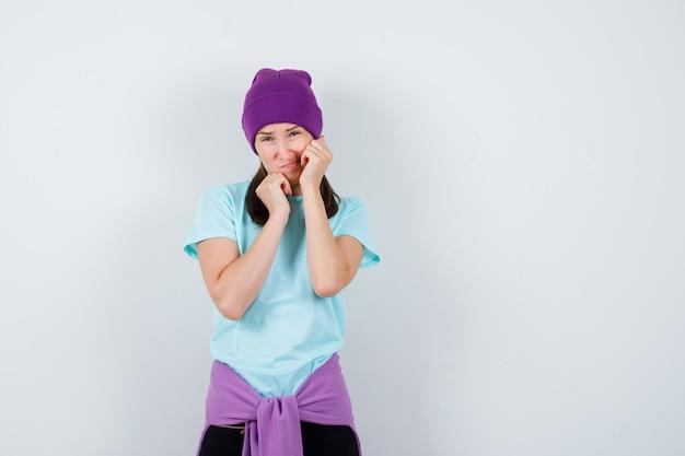 Portrait d'une femme merveilleuse gardant une main sur le menton et la joue l'autre en blouse, bonnet et à la vue de face effrayée
