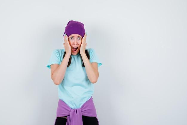 Portrait d'une femme merveilleuse avec les mains sur les joues, ouvrant la bouche en blouse, bonnet et regardant horrifié la vue de face