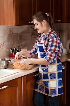 Portrait de femme mettant la carotte râpée dans un bol