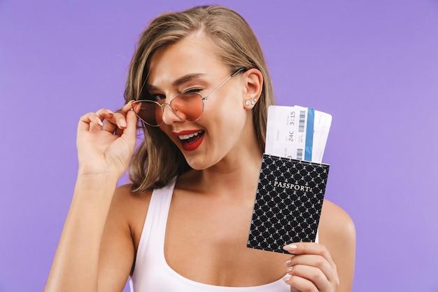 Portrait de femme mignonne brune en vêtements d'été et lunettes de soleil souriant et tenant des billets de passeport et de vacances,