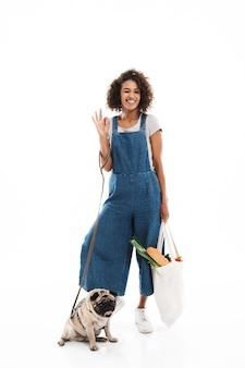 Portrait d'une femme mignonne faisant un clin d'œil et faisant des gestes ok chanter tout en se tenant avec son carlin et son sac à provisions isolés sur un mur blanc