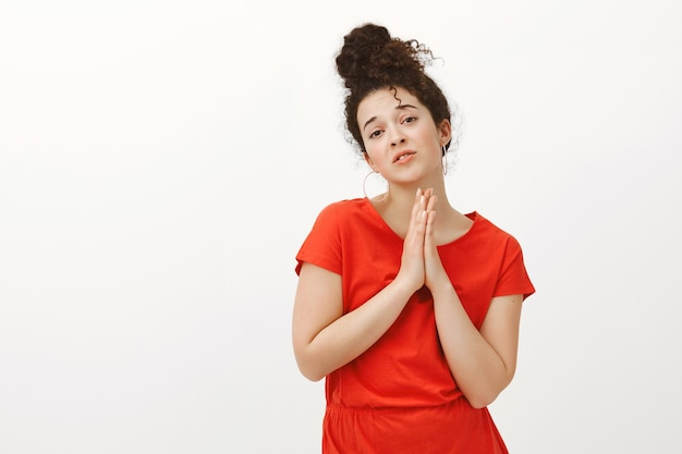 Portrait de femme mignonne gourmande aux cheveux bouclés en robe rouge, tenant les mains en priant avec les paumes ensemble sur la poitrine, implorant faveur ou aide