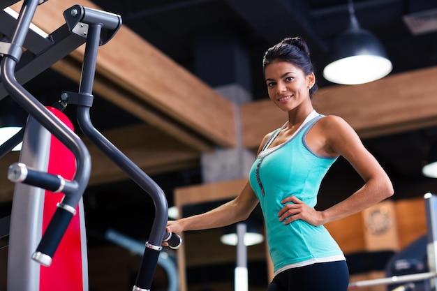 Portrait d'une femme mignonne heureuse debout dans une salle de fitness