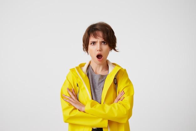 Portrait de femme mignonne indignée en manteau de pluie jaune, regarde la caméra avec des expressions émerveillées, avec la bouche grande ouverte et les bras croisés, semble mécontente, se tenir debout sur un mur blanc.