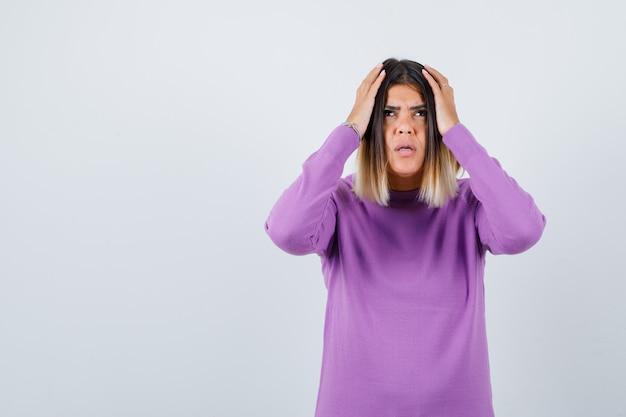 Portrait d'une femme mignonne avec les mains sur la tête en pull violet et regardant la vue de face baissée