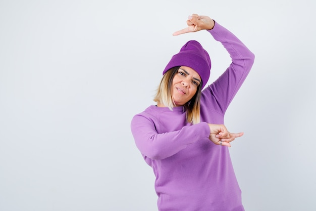 Portrait d'une femme mignonne pointant à gauche et à droite dans un pull, un bonnet et à la vue de face confiante
