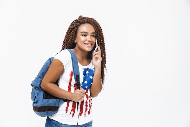 Portrait d'une femme mignonne portant un sac à dos souriant et parlant au téléphone portable tout en se tenant isolé contre un mur blanc