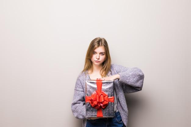 Portrait d'une femme mignonne souriante ouvrant une boîte-cadeau