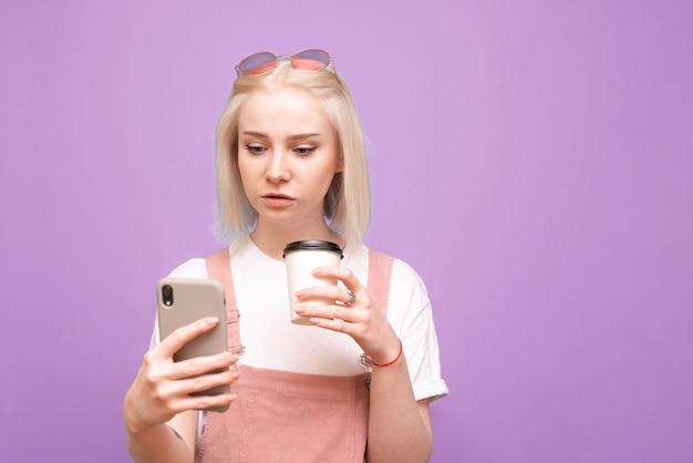 Portrait de femme mignonne avec une tasse de café dans ses mains, utilisez un smartphone