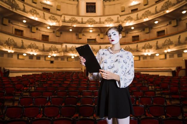 Portrait, femme, mime, debout, auditorium, tenue, script