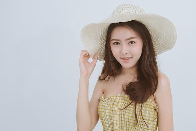 Portrait de femme mince asiatique portant un grand chapeau souriant regarde la caméra sur fond isolé blanc.