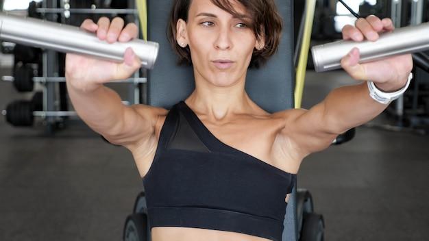 Portrait De Femme Mince Fait Des Exercices Pour Les Muscles Des Bras Sur La Machine D'entraînement. Elle Est Assise Et Repousse Quelques Représentants. Entraînement Sportif Dans La Salle De Gym, Vue De Face Photo Premium