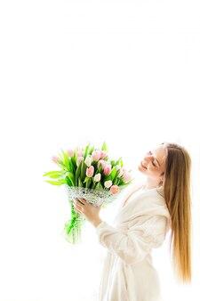 Portrait de femme mince sexy assez élégante en robe blanche ayant un gros bouquet de tulipes en mains isolés.