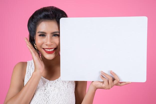 Portrait de femme de mode affichant une bannière blanche