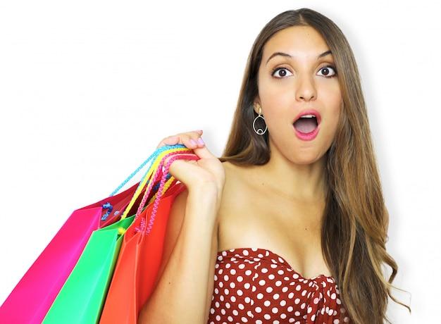 Portrait d'une femme de mode assez choquée tenant des sacs à provisions