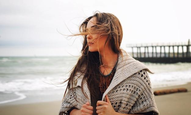 Portrait de femme de mode contre une jetée sur une plage de la mer, mode en plein air d'automne