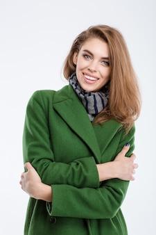Portrait d'une femme de mode souriante en manteau regardant la caméra isolée sur fond blanc