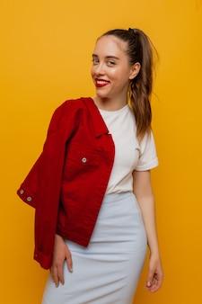 Portrait de femme moderne élégante en jupe bleue et veste rouge et souriant sur jaune