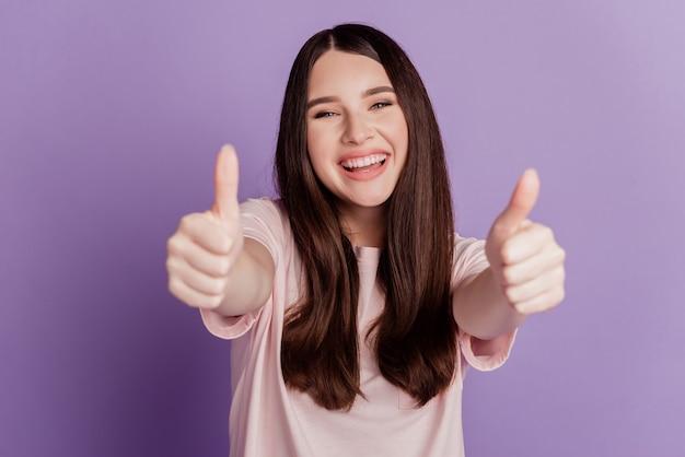 Portrait de femme montrant les pouces vers le haut sourire rayonnant sur bakground violet
