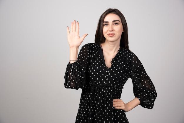 Portrait de femme montrant sa main sur gris.