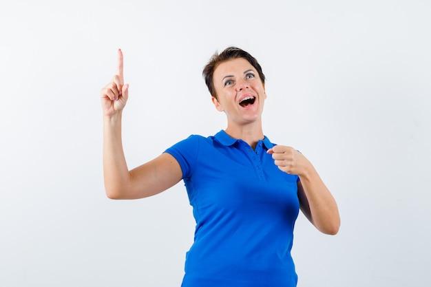 Portrait de femme mûre pointant vers le haut, faisant semblant de tenir quelque chose en t-shirt bleu et à la vue de face heureuse