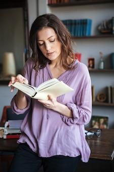 Portrait d'une femme mûre réfléchie lisant un livre