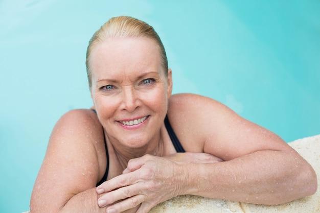 Portrait de femme mûre se penchant sur la piscine