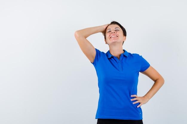 Portrait de femme mûre tenant la main sur la tête en t-shirt bleu et à la vue de face heureux