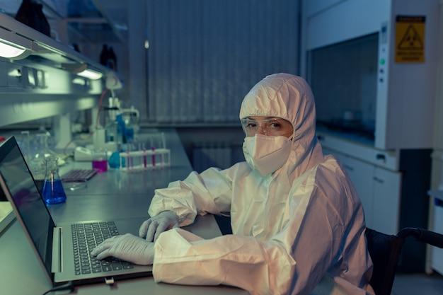 Portrait d'une femme mûre en vêtements de travail protecteurs regardant la caméra tout en tapant sur un ordinateur portable à la table du laboratoire