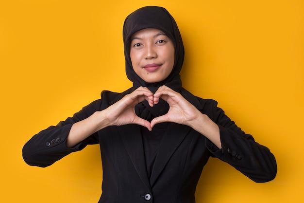 Portrait de femme musulmane asiatique montrant signe de coeur sur l'espace jaune