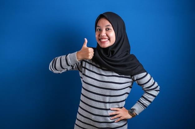 Portrait d'une femme musulmane asiatique souriante et souriante montre un geste de signe de doigt ok, sur fond bleu