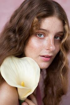Portrait de femme mystérieuse aux taches de rousseur tenant une fleur