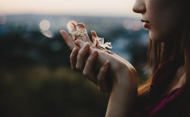 Portrait de femme la nature. jolie femme joue avec un pissenlit