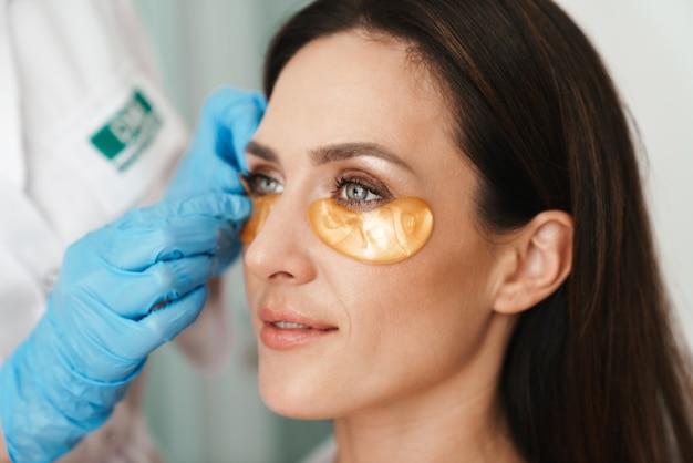 Portrait de femme obtenant une procédure cosmétique avec des patchs par un spécialiste en salon de beauté