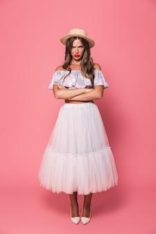 Portrait de femme offensée bouleversée portant un chapeau de paille et une jupe moelleuse faisant la moue avec ressentiment avec les bras croisés
