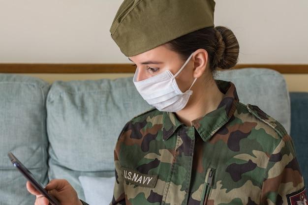 Portrait d'une femme officier de l'armée en uniforme et masque chirurgical. regardant le téléphone portable
