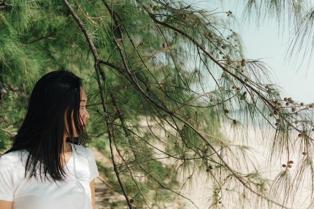 Portrait de femme à l'ombre d'un pin en été.