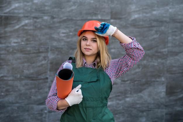 Portrait de femme ouvrier builder debout porter l'uniforme et la barre. rénovation de la maison.