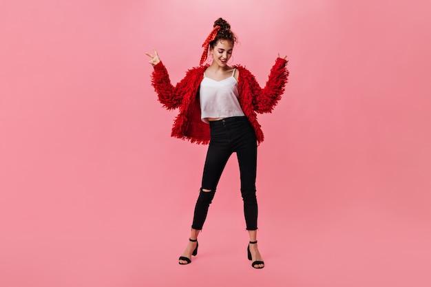 Portrait de femme en pantalon sombre et manteau rouge dansant sur isolé