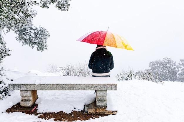 Portrait d'une femme avec un parapluie coloré assis sur un banc dans un paysage enneigé.