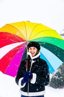 Portrait d'une femme avec un parapluie coloré heureux lors d'une chute de neige.
