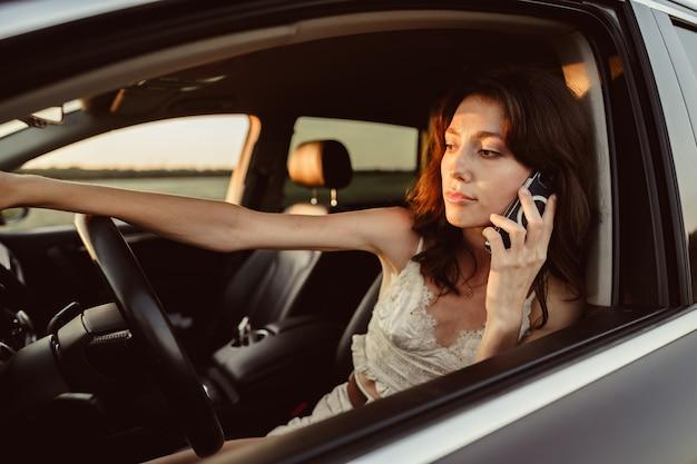 Portrait de femme parlant au téléphone portable tout en conduisant sa voiture
