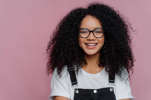Portrait d'une femme à la peau foncée avec des cheveux croquants, sourit avec bonheur, porte des lunettes optiques, des vêtements décontractés