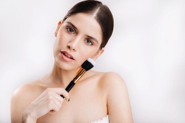 Portrait de femme à la peau propre sur un mur isolé. naturellement belle fille aux yeux verts sans maquillage posant avec un pinceau pour fond de teint.