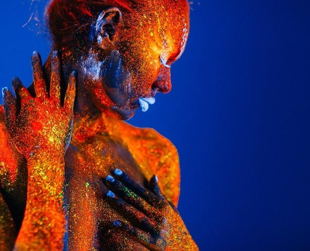 Portrait d'une femme peinte en poudre fluorescente.