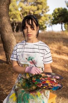 Portrait de femme peintre à l'extérieur avec palette