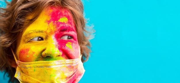 Portrait d'une femme en peinture holi de couleur sèche et masque de protection médicale