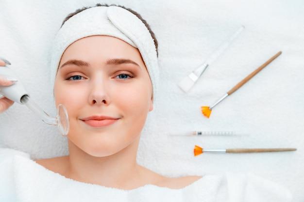 Portrait de femme pendant la procédure de cosmétologie darsonval pour les soins de la peau se trouve avec une seringue d'injection de beauté masque facial brosses cosmétiques outil spa appareils sur serviette blanche esthéticienne dans un salon de beauté